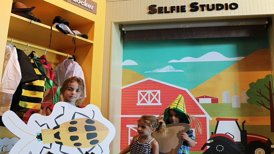 "WinField Ag Technology Applications Lead Joel Wipperfurth's children play in the ""Selfie Station"" exhibit during the grand opening tour for the media. Wipperfurth was closely involved in the development of the WinField Crop Adventure."