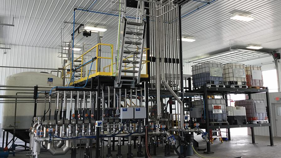 A liquid mass flow system by Kahler Automation dispenses product in the load out line adjacent to the truck bay equipped with top and bottom fill.